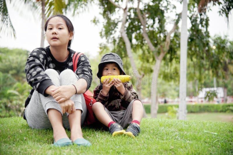 De jonge zitting van de moederzoon op gras: Close-up royalty-vrije stock afbeeldingen