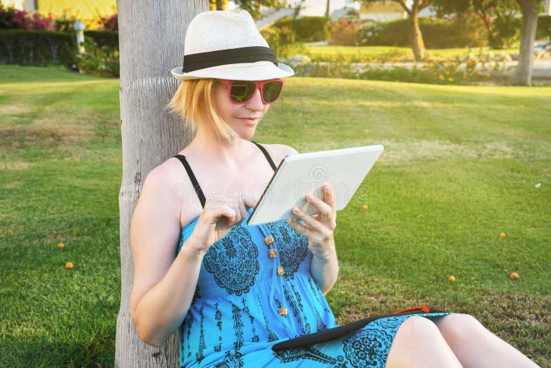 De jonge zitting van de studentenvrouw op een groen gras in een park en een holding een tabletcomputer stock fotografie
