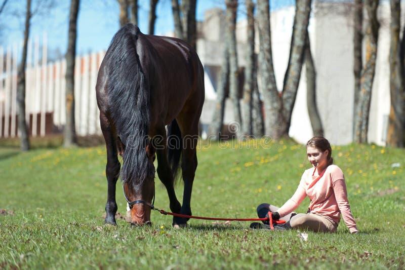 De jonge zitting van de tienereigenaar dicht bij haar favoriet paard stock afbeelding