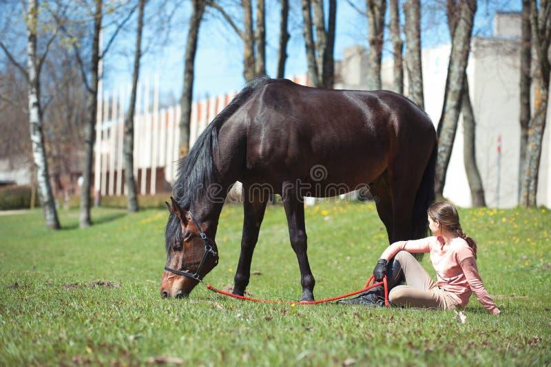 De jonge zitting van de tienereigenaar dicht bij haar favoriet paard stock foto's