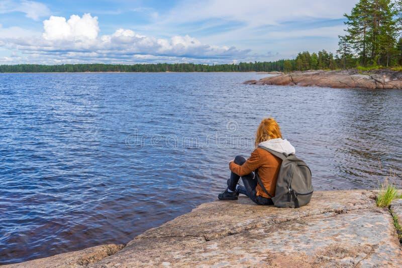 De jonge zitting van de toeristendame op noordelijke meerkust in de zomerdag Tiener die en mooi landschap ontspannen bewonderen royalty-vrije stock afbeeldingen