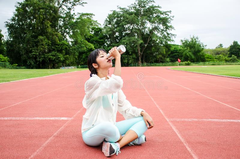 De jonge zitting van de vrouwenatleet op renbaan en drinkwater in fles royalty-vrije stock afbeeldingen