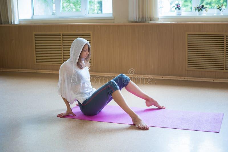 De jonge zitting van de vrouwenturner op de yogamat in de dansstudio stock fotografie