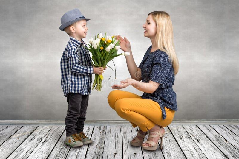 De jonge zoon geeft zijn geliefde moeder een boeket van mooie tulpen De lente, concept familievakantie De dag van vrouwen `s stock foto