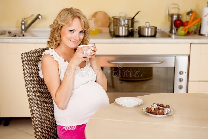 De jonge zwangere vrouw drinkt thee met snoepjes royalty-vrije stock fotografie