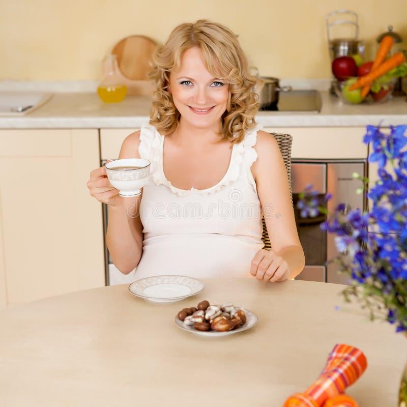 De jonge zwangere vrouw drinkt thee met snoepjes bij keuken royalty-vrije stock afbeelding