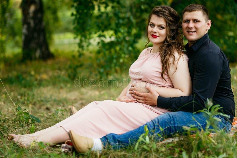 De jonge zwangere vrouw en haar echtgenoot omhelzen in groen Park op gras stock fotografie