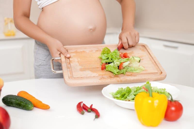 De jonge zwangere vrouw kookt gezond voedsel stock fotografie