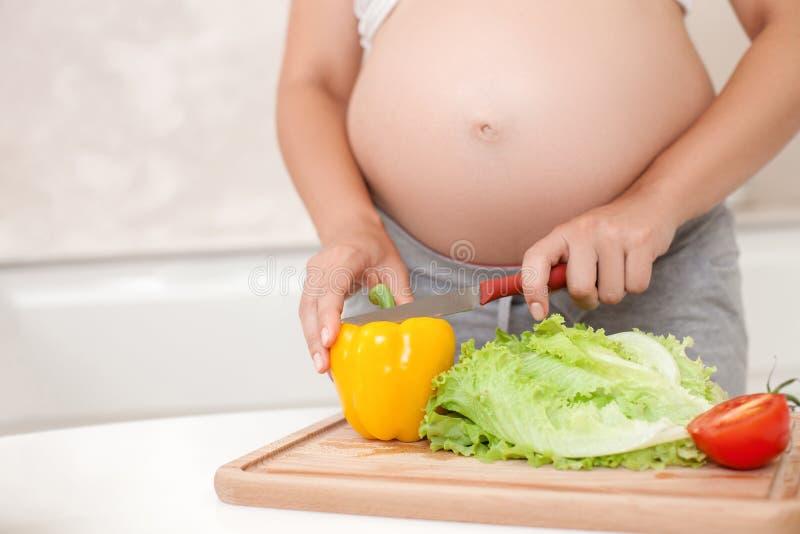 De jonge zwangere vrouw maakt een salade in keuken stock foto's