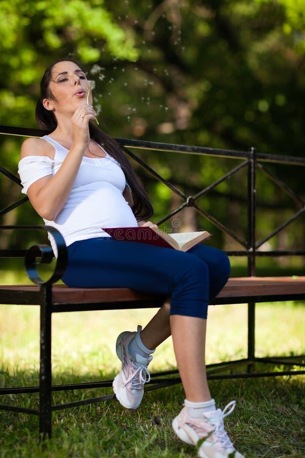 De jonge zwangere vrouw met boek zit in het park. stock afbeelding