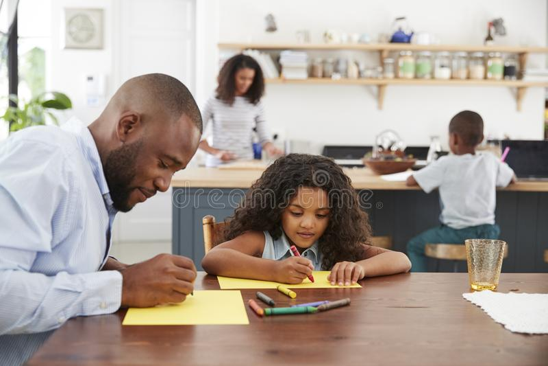 De jonge zwarte familie van vier bezig in hun keuken, sluit omhoog stock afbeelding