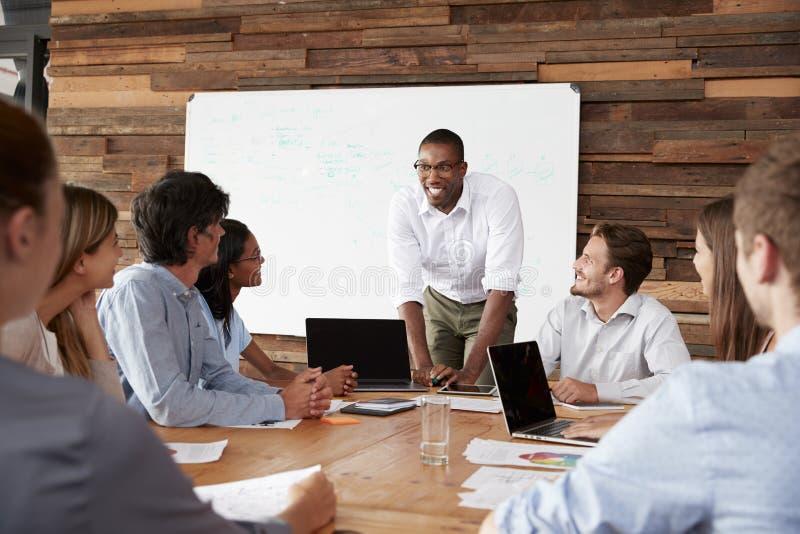 De jonge zwarte mens bevindt zich richtend collega's op een vergadering stock afbeelding