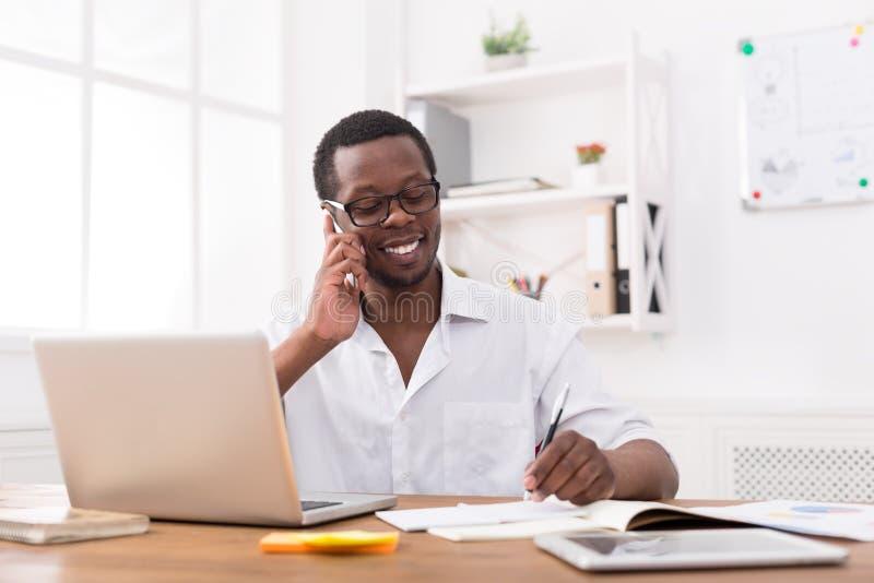 De jonge zwarte mobiele telefoon van de zakenmanvraag in modern wit bureau royalty-vrije stock afbeeldingen