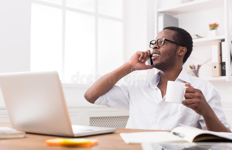 De jonge zwarte mobiele telefoon van de zakenmanvraag in modern wit bureau stock afbeeldingen