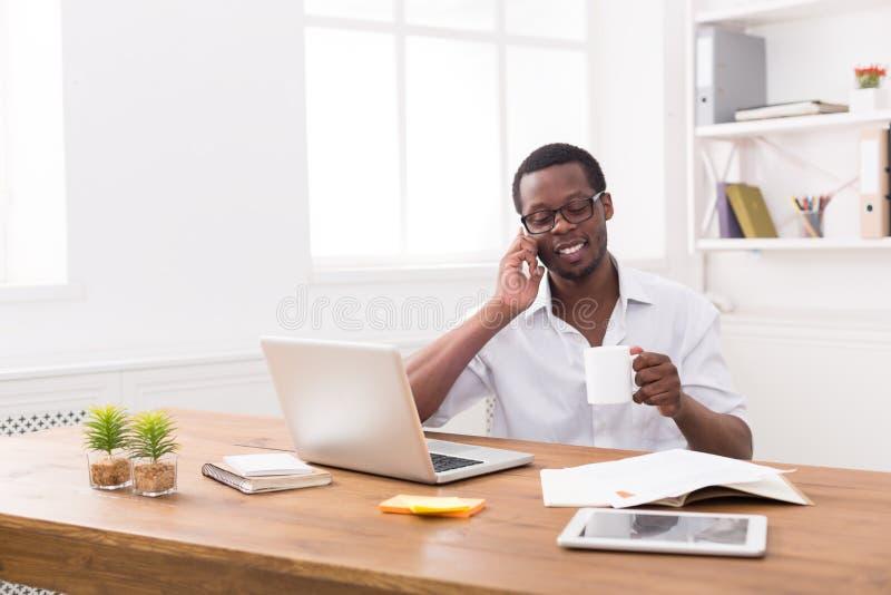 De jonge zwarte mobiele telefoon van de zakenmanvraag in modern wit bureau stock foto's