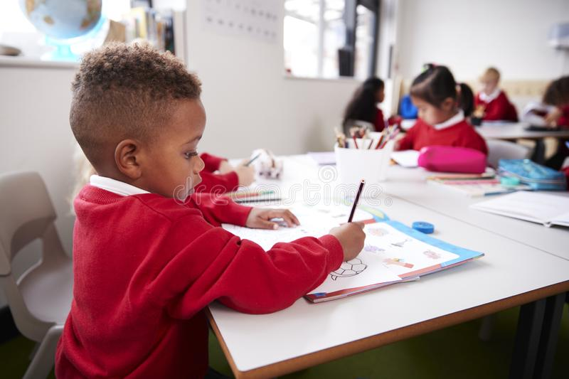 De jonge zwarte schooljongen die school eenvormige zitting dragen bij een bureau in een het klaslokaaltekening van de zuigelingss stock afbeelding