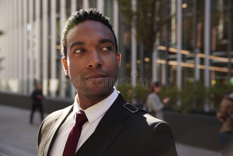 De jonge zwarte zakenman die zwart kostuum dragen die zich op straat glimlachen bevinden, die sluit omhoog weg eruit zien royalty-vrije stock foto's