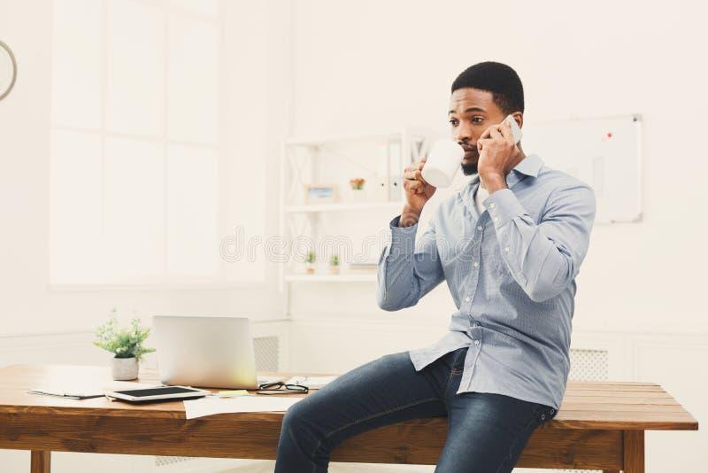 De jonge zwarte zakenman heeft mobiele telefoonbespreking royalty-vrije stock fotografie