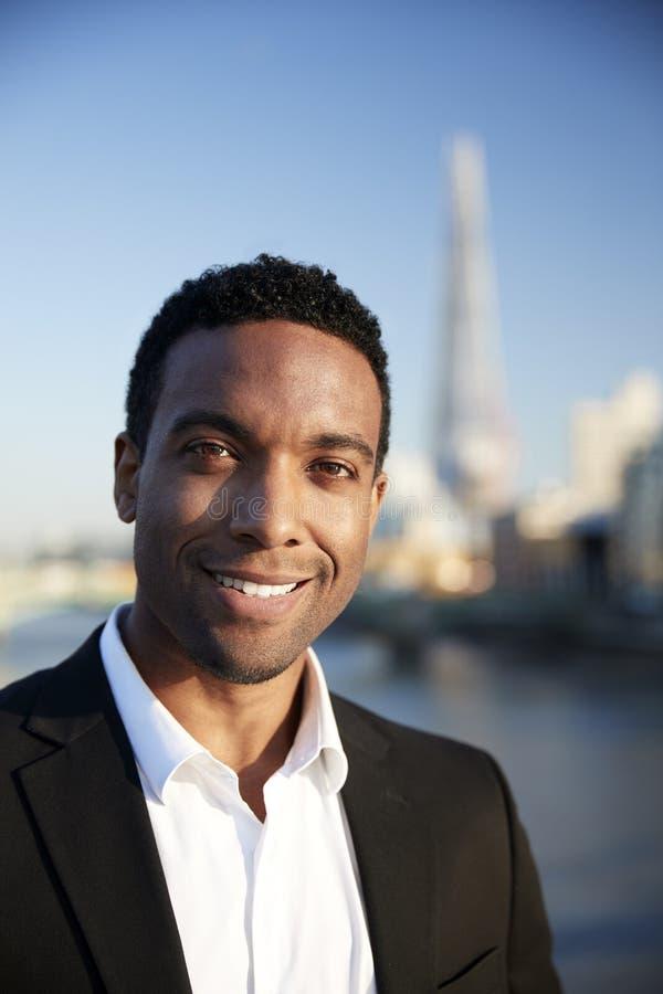 De jonge zwarte zakenman in slimme toevallige kleding die zich door de Rivier Theems in Londen bevinden die aan camera glimlachen stock foto's