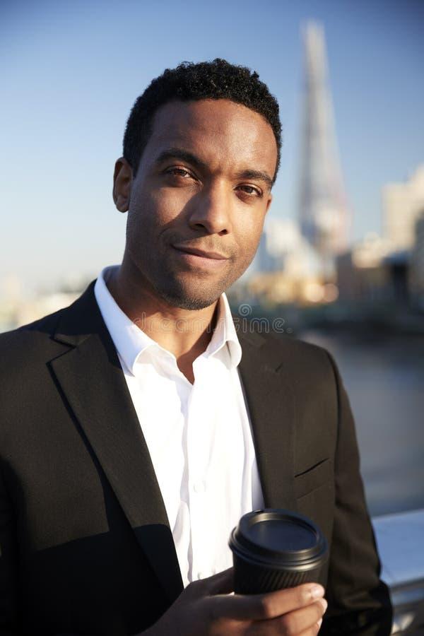 De jonge zwarte zakenman in slimme toevallige kleding die zich door de Rivier Theems in Londen bevinden die een meeneemkoffie hou stock foto's