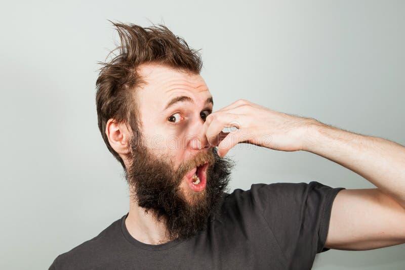 De jongelui baerded kerel dichte neus van een stank op grijze achtergrond stock afbeelding