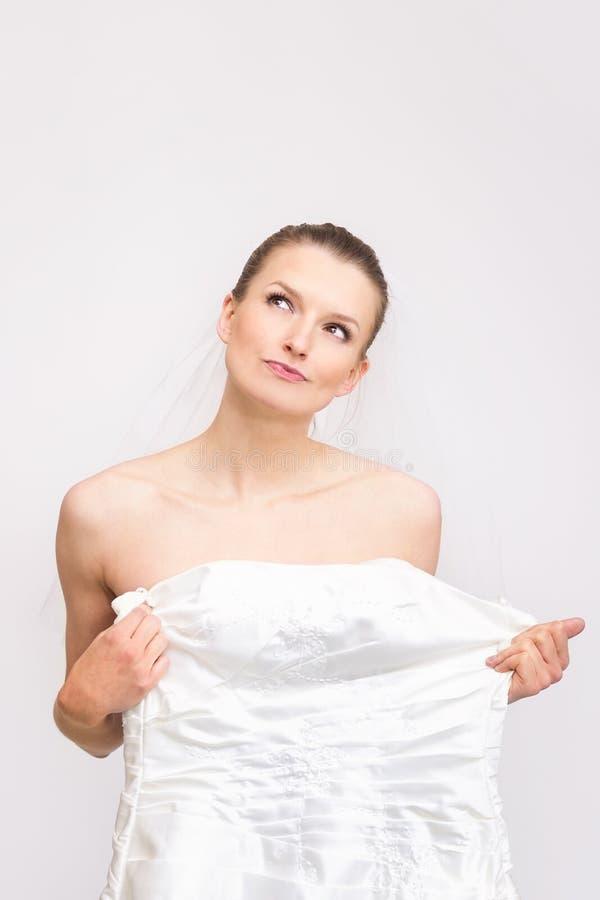 De jongelui bruid-aan-probeert op haar toga - controlerend de kleding royalty-vrije stock afbeelding