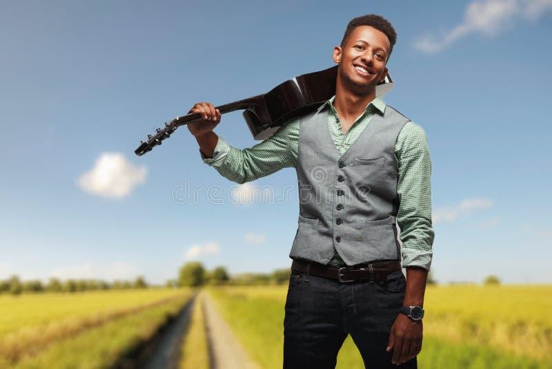 De jongelui die hipster bemant het stellen vreugdevol met gitaar op schouder op vage landschapsachtergrond glimlachen royalty-vrije stock foto's