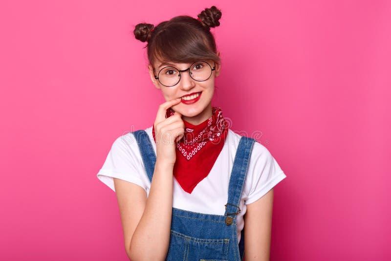 De jongelui die mooi schoolmeisje met lang chocoladehaar glimlachen, houdt wijsvinger op lippen Donkere haired student cames teru stock afbeeldingen