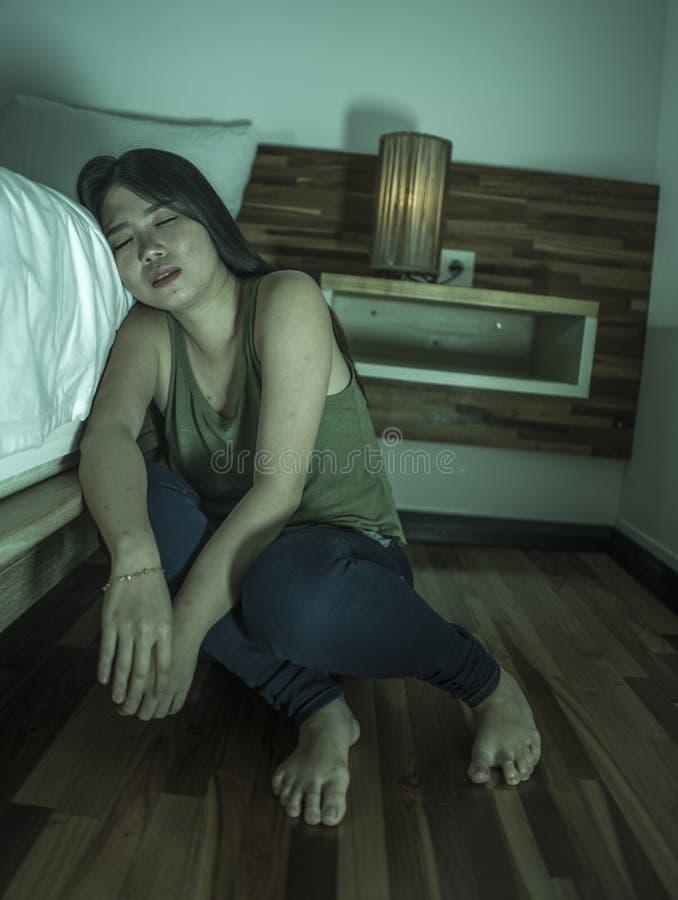 De jongelui drukte en droevige Aziatische Koreaanse vrouwenzitting op vloer bij slaapkamer naast bed in die depressie aan problee stock fotografie