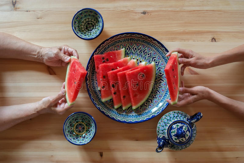 De jongelui en de bejaarden met watermeloen in van hem dient een Aziatische koffie, Samarkand, Oezbekistan in royalty-vrije stock afbeeldingen