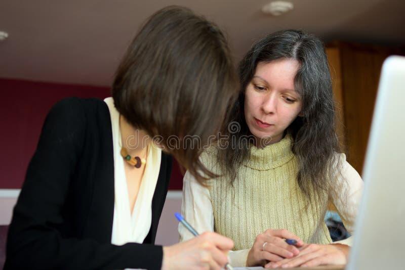 De jongelui kleedde smartly dame helpt een andere jonge dame om met documenten te werken, vormen en teken vullen stock afbeelding