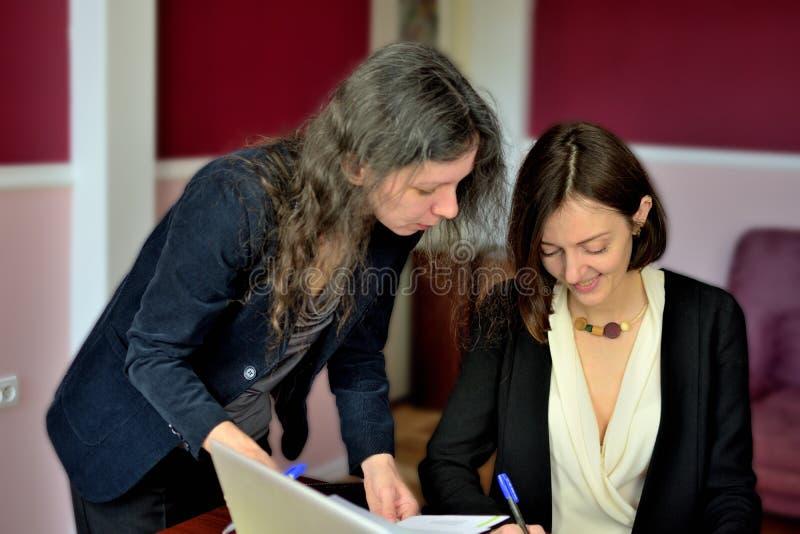 De jongelui kleedde smartly dame helpt een andere jonge dame om met documenten te werken, vormen en teken vullen stock afbeeldingen