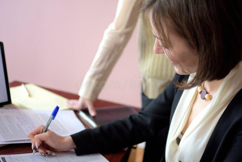 De jongelui kleedde smartly dame helpt een andere jonge dame om met documenten te werken, vormen en teken vullen royalty-vrije stock afbeeldingen