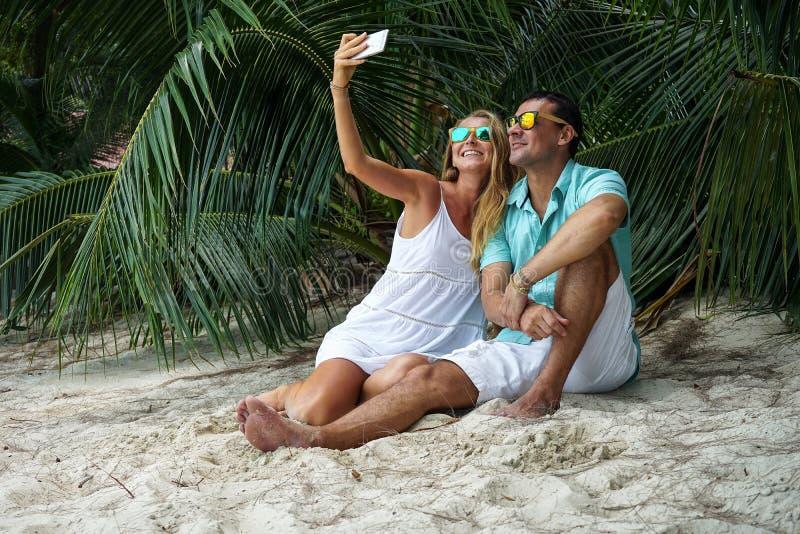 De jongelui koppelt, zitten de vrouw en de man op het strand en zullen selfies gekleed in heldere kleren en in zonnebril nemen stock afbeelding
