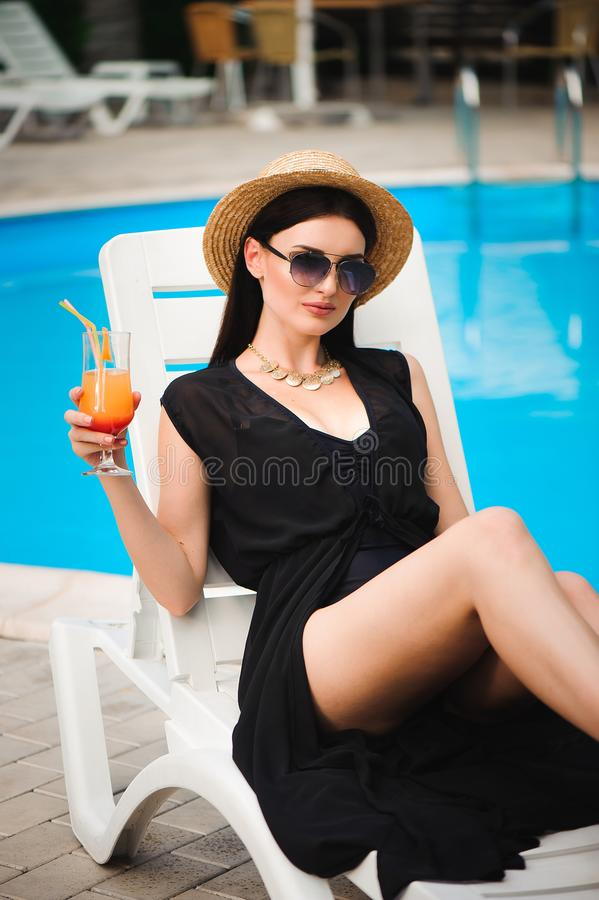 De jongelui looit model in modieuze de zomeruitrusting genietend pool van partij, die smakelijke alcoholcocktail houden royalty-vrije stock fotografie