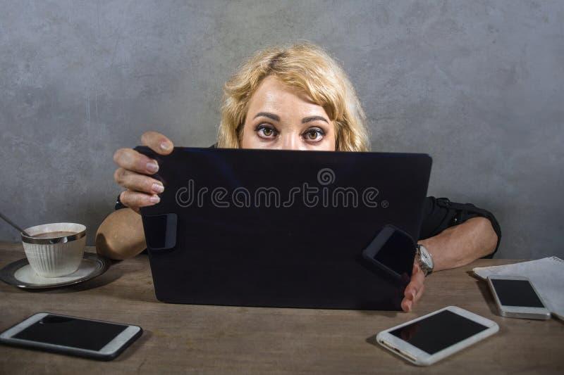 De jongelui verraste en beklemtoonde bedrijfsvrouw die bij die bureau intens aan het computerscherm kijken door mobiele telefoons stock foto's