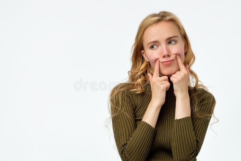 De jongelui verstoort krullende blondevrouw die valse glimlach maken stock foto's