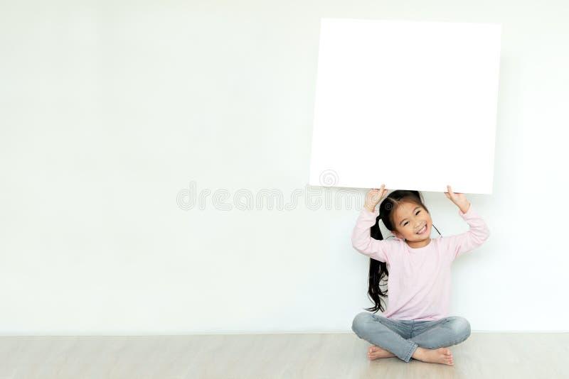 De jongelui weinig Aziatisch meisje of jong geitje geniet van tegenhoudend lege witte aanplakbiljetraad voor media banner, bedrij royalty-vrije stock afbeeldingen