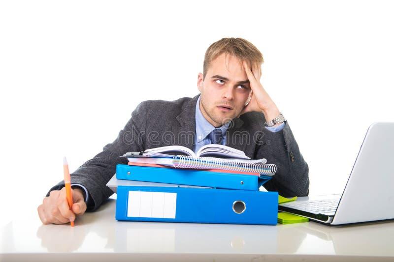 De jongelui werkte zich en overweldigde zakenman in spanning het leunen op uitgeput over en gedeprimeerde bureauomslag stock afbeelding