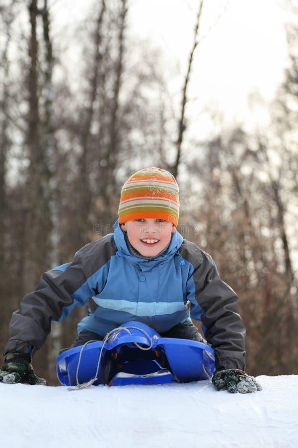 De jongen is aandrijving van heuvel in de winter op sleeën van plan stock foto's