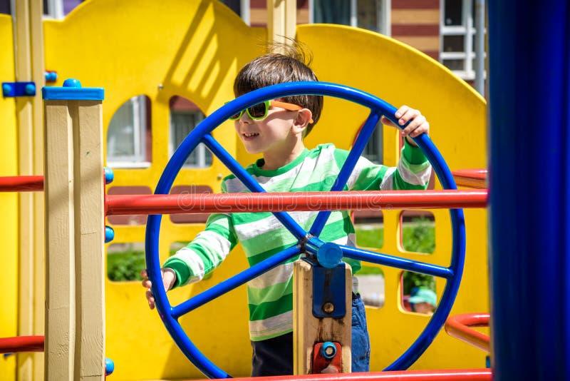 De jongen als kapitein of de zeelieden spelen in openlucht op het schip op zonnige dag Het jonge geitje heeft heel wat pret Het s royalty-vrije stock afbeelding