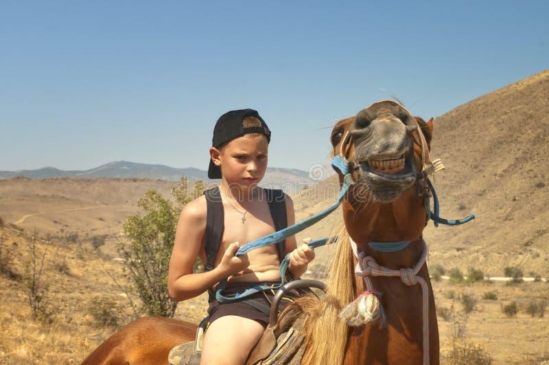 De jongen bedwingt een paard. stock fotografie