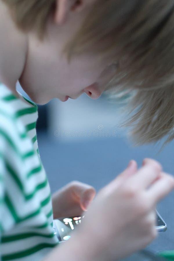 De jongen bekijkt het scherm van een mobiele telefoon stock fotografie