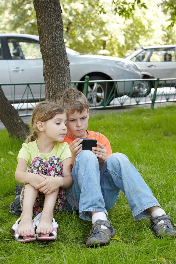De Jongen Bekijkt Het Telefoonscherm, Zit De Zuster Naast Hem Stock Foto's