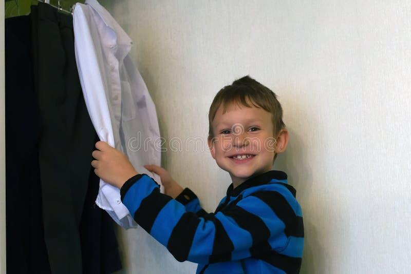 de jongen bekijkt zijn kleren royalty-vrije stock afbeelding