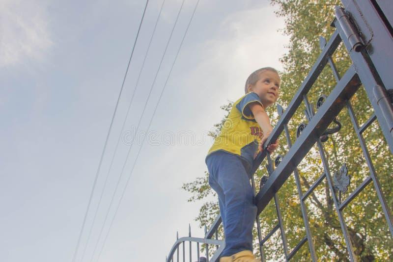 De jongen beklom op de omheining Het kind beklimt op de poort, Fe royalty-vrije stock fotografie