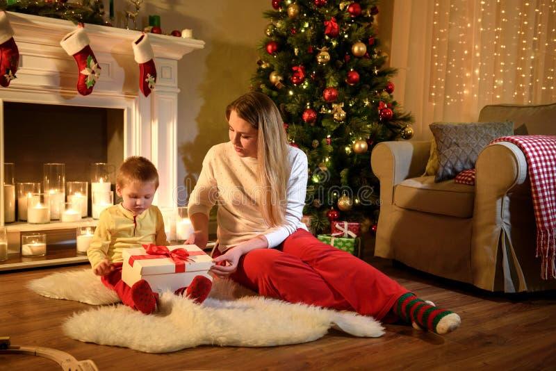 De jongen is bereid om zijn aanwezige Kerstmis te openen stock afbeelding
