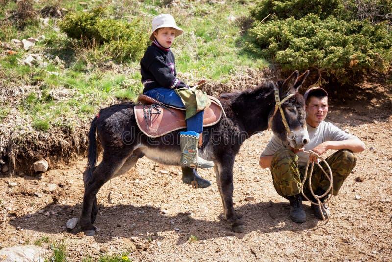 De jongen berijdt een ezel royalty-vrije stock fotografie