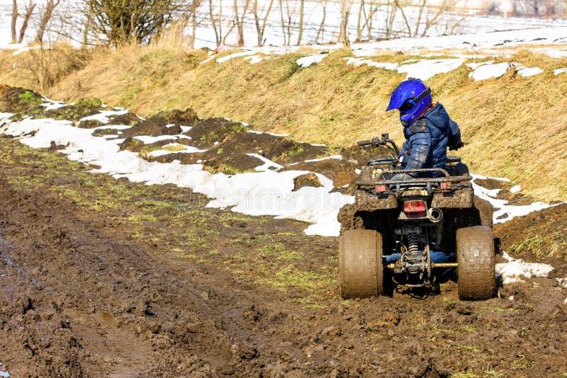 De jongen berijdt een off-road ATV stock fotografie