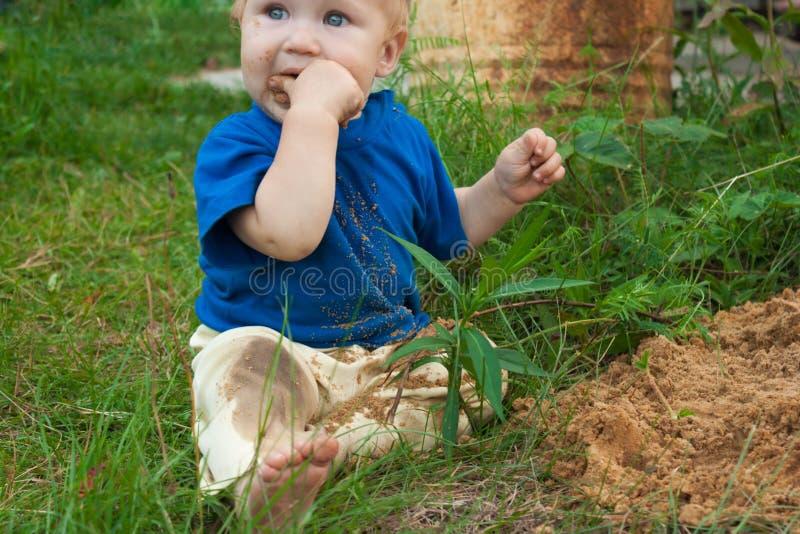 De jongen bestudeert het natuurlijke materiaal dat hem interesseert royalty-vrije stock afbeeldingen